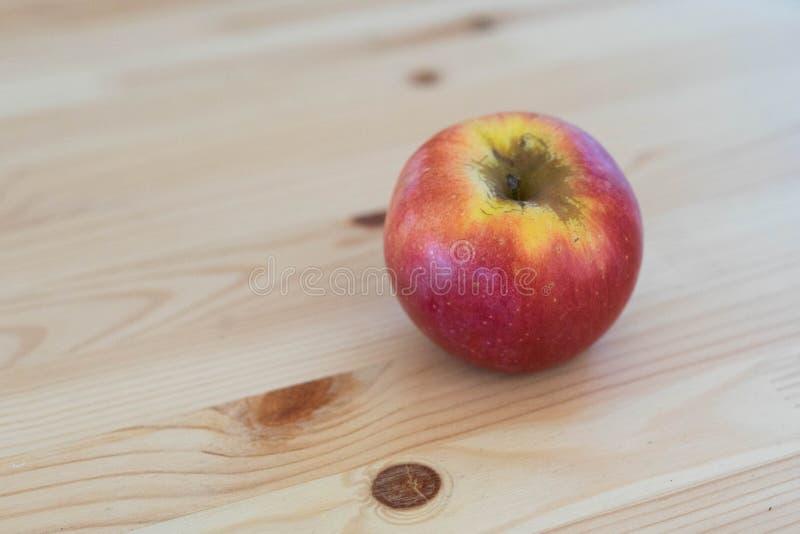 Runder roter Apfel auf hölzernem Hintergrund stockbild