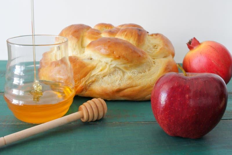 Runder süßer Challah, Honigglas, roter Apfel und Granatapfel auf einem t lizenzfreies stockbild