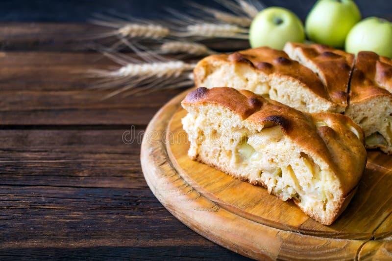 Runder selbst gemachter Apfelkuchen, Schuster, braune Betty, Apple Charlotte auf hölzernem Hintergrund mit Äpfeln lizenzfreie stockbilder