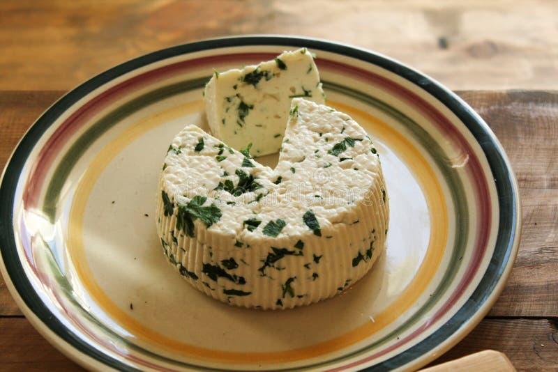Runder selbst gemachter frischer natürlicher Käse, der auf einer Platte auf einem Holztisch liegt lizenzfreie stockfotografie