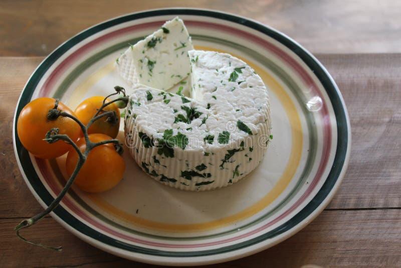 Runder selbst gemachter frischer natürlicher Käse, der auf einer Platte nahe bei der Tomate auf einem Holztisch liegt stockfotos