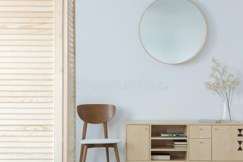 Runder Spiegel über Holzstuhl und Kabinett im minimalen Vorzimmer Innen mit Dekor lizenzfreies stockbild