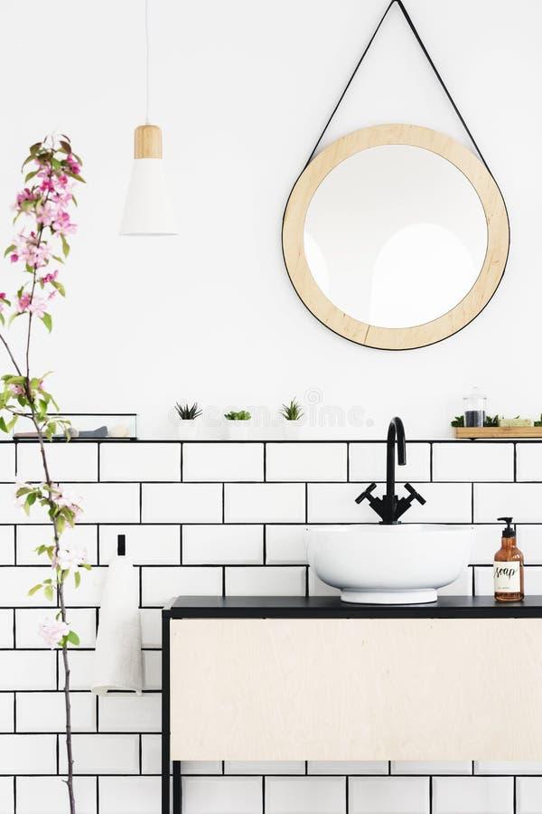 Runder Spiegel über Waschbecken im weißen Badezimmerinnenraum mit rosa Blumen Reales Foto lizenzfreies stockfoto