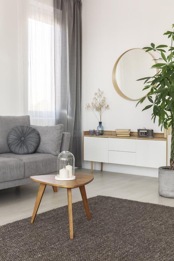 Runder Spiegel im Holzrahmen auf leerer weißer Wand des hellen Wohnzimmerinnenraums lizenzfreie stockfotos