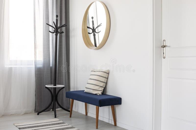 Runder Spiegel im Holzrahmen auf leerer weißer Wand des hellen Wohnzimmerinnenraums stockbild