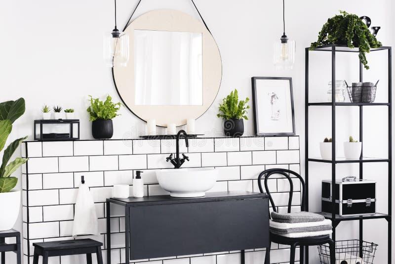 Runder Spiegel zwischen Anlagen im Schwarzweiss-Badezimmerinnenraum mit Plakat und Stuhl Reales Foto stockfotos