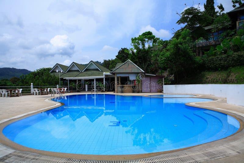 Runder Swimmingpool, Sonnenruhesessel nahe bei dem Garten und Pagode stockbild