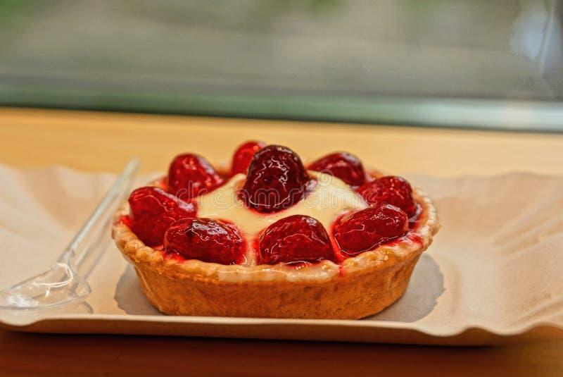 runder Tartletkuchen mit roten Erdbeeren auf einem grauen Papierbehälter mit einem kleinen Löffel lizenzfreie stockfotos
