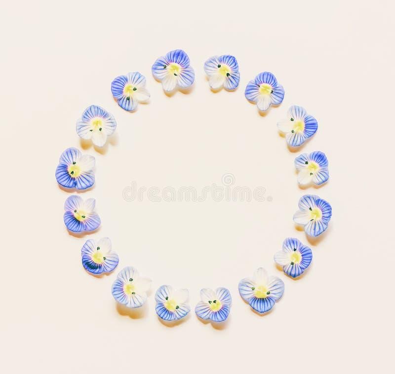 Runder Weinleserahmen gemacht von den kleinen blauen Blumen auf einem weißen Hintergrund mit Raum für Text stockfotografie