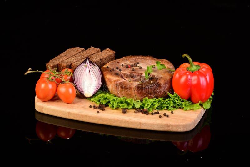 Rundes Fleischsteak auf einem hölzernen Brett mit Gemüse stockfotos