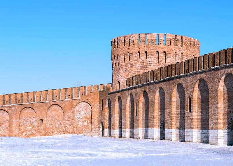Rundes großes Turmhoch des Ziegelsteines mit einer crenellated Wand mit schützender Wand der Bögen des Kremls gegen einen blauen  stockfotografie