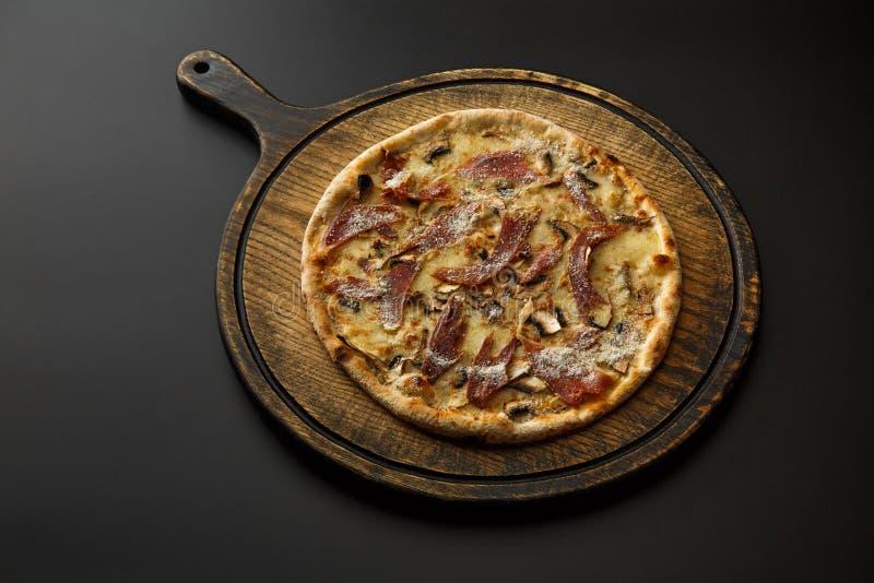 Rundes hölzernes Brett mit der Pizza lokalisiert auf einem schwarzen Hintergrund lizenzfreies stockfoto