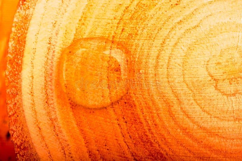 Rundes Wasser fällt in Nahaufnahme auf hölzernem Hintergrund stockbild