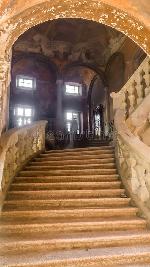 Decaying staircase and hall of a former palazzo in Piacenza, Italy. Rundown interior of a former palazzo in Piacenza, Italy. Still stylish royalty free stock photo