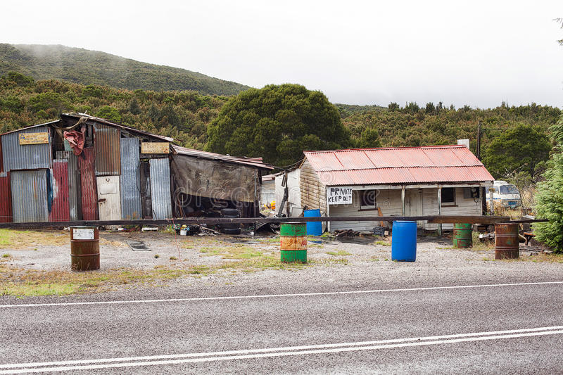 Rundown and ramshackle home. Queenstown, Australia-March 5, 2012. Rundown and ramshackle home and sheds on a property on the outskirts of the west coast township stock photos