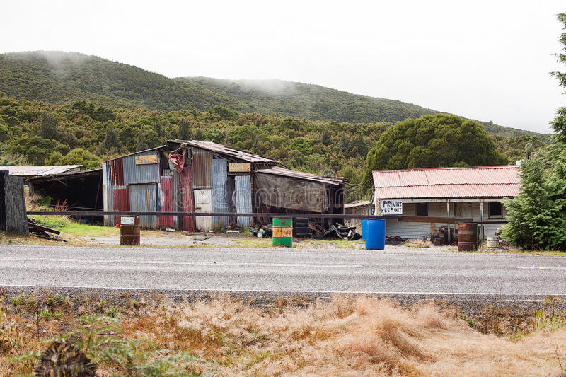 Rundown and ramshackle home. Queenstown, Australia-March 5, 2012. Rundown and ramshackle home and sheds on a property on the outskirts of the west coast township royalty free stock photos