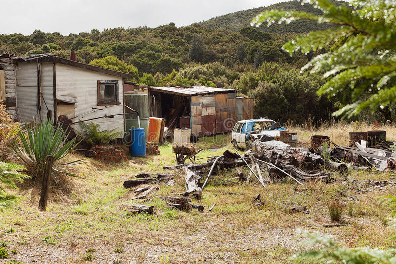 Rundown and ramshackle home. Queenstown, Australia-March 5, 2012. Rundown and ramshackle home and sheds on a property on the outskirts of the west coast township royalty free stock image