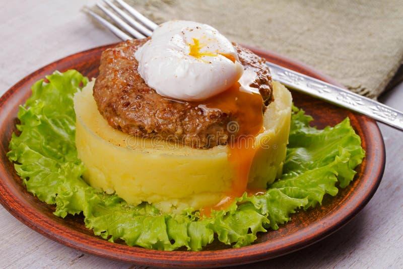 Rundvlees en varkensvleespasteitje met gestroopt ei, gebroken aardappel en sla stock fotografie