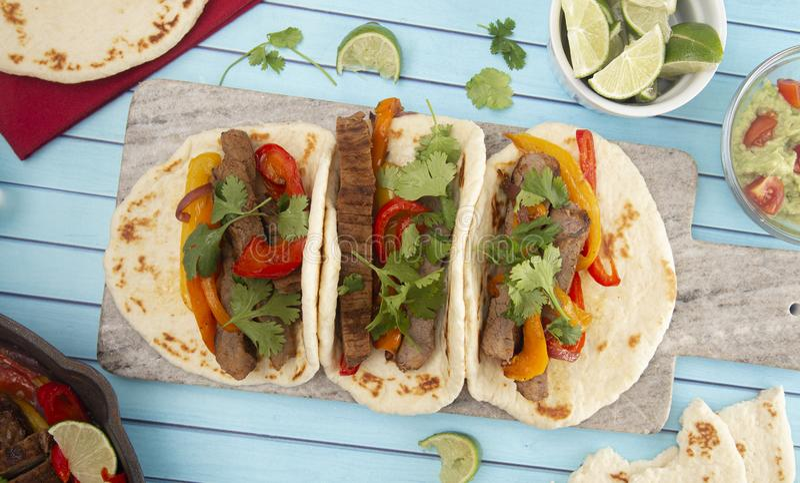 Rundvlees Fajitas met Groene paprika's op een Blauwe Houten Lijst stock fotografie