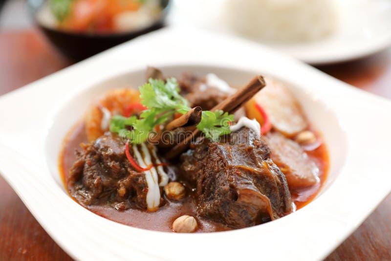 Rundvlees massaman kerrie met rijst en salade op houten lijst, Thais voedsel stock afbeeldingen