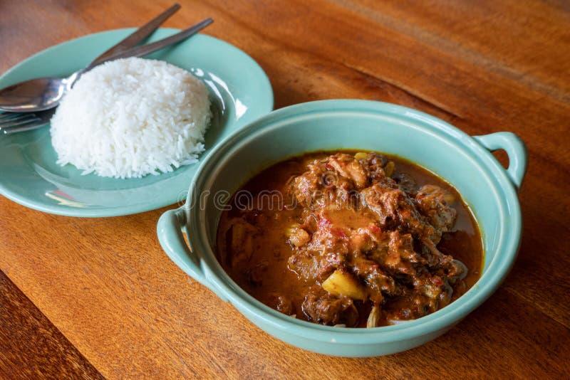 Rundvlees massaman kerrie met rijst op houten lijst, Thais voedsel stock foto's