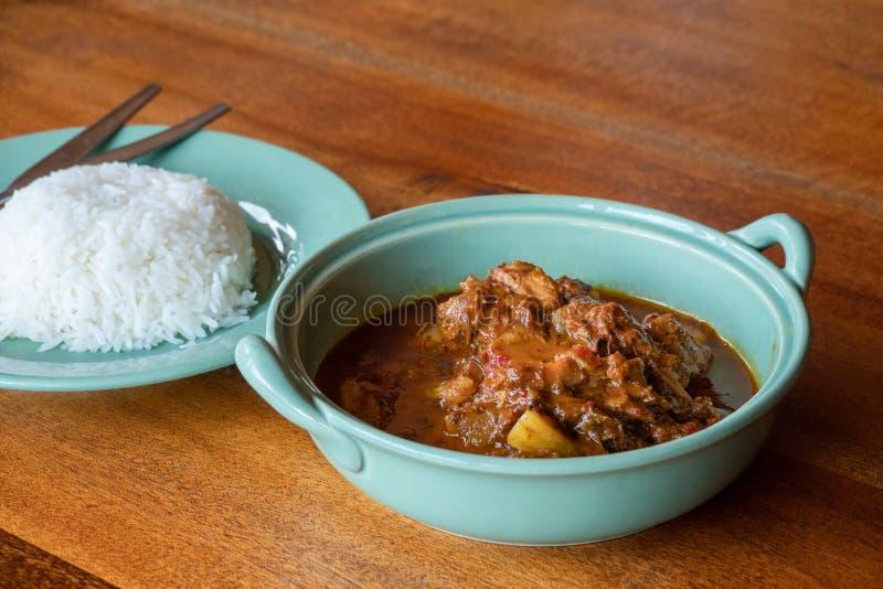 Rundvlees massaman kerrie met rijst op houten lijst, Thais voedsel stock afbeeldingen