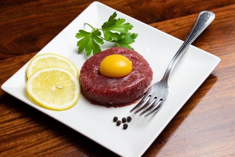 Rundvlees tartare met eierdooier op een witte plaat royalty-vrije stock fotografie