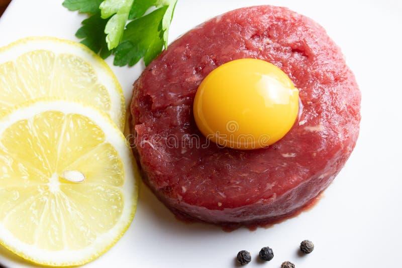 Rundvlees tartare met eierdooier op een witte plaat royalty-vrije stock foto's