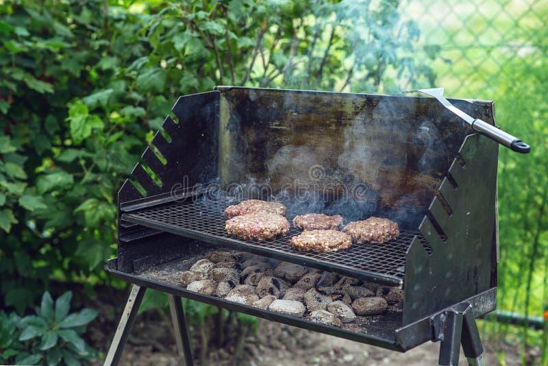 Rundvlees of varkensvlees het vlees roostert burgers voor voorbereid die hamburger bij bbq de rookgrill wordt geroosterd in tuin stock foto