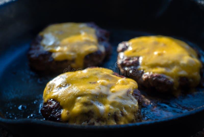 Rundvleesburgers op pan met smeltende cheddarkaas stock fotografie