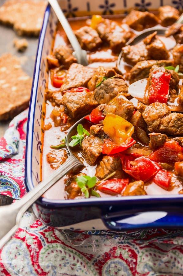 Rundvleesgoelasj met groenten in blauwe braadpanschotel met lepel royalty-vrije stock foto's