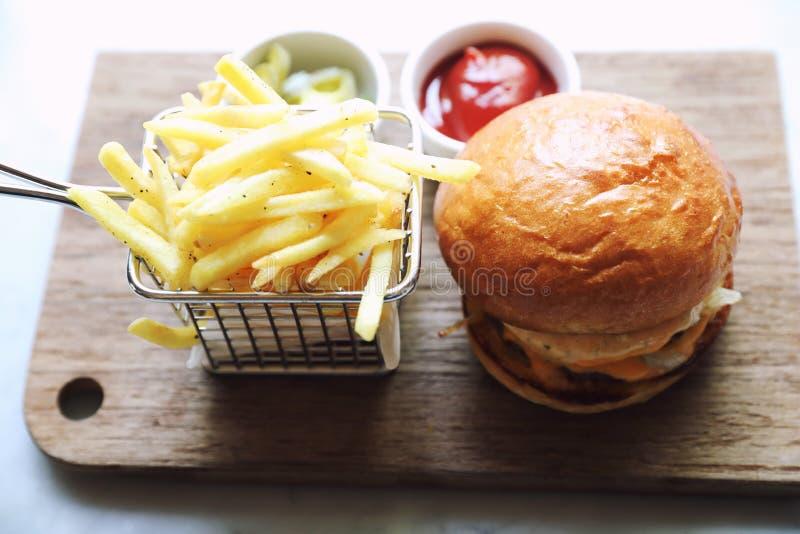 Rundvleeshamburger met gebraden gerechten en ketchup, snel voedsel royalty-vrije stock foto's