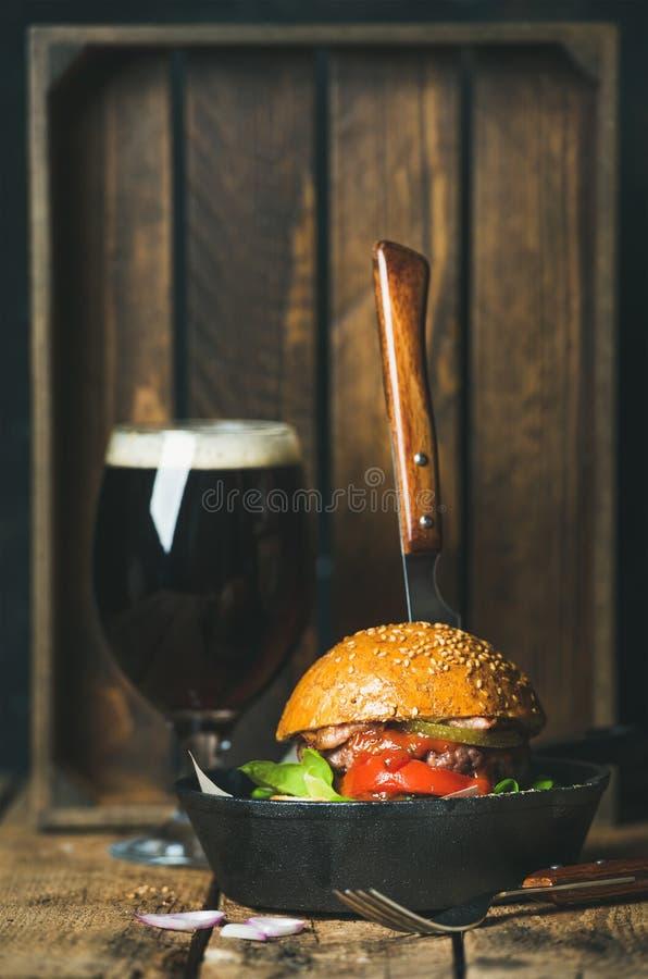 Rundvleeshamburger met knapperig bacon in pan en donker bier royalty-vrije stock foto's