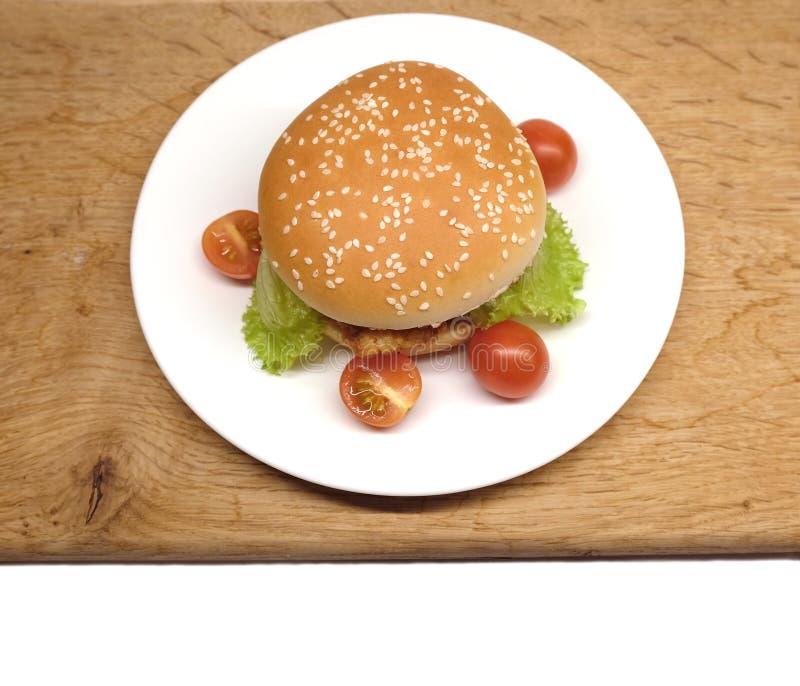 Rundvleeshamburger met salade en kleine tomaten op een plaat stock foto's