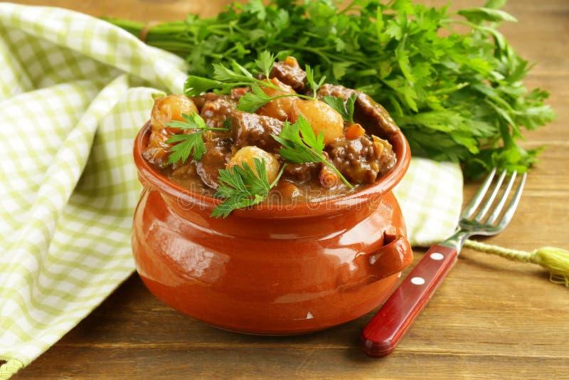 Rundvleeshutspot met groenten en kruiden in een kleipot royalty-vrije stock afbeelding