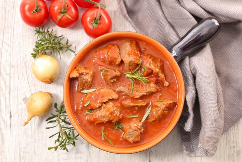 Rundvleeshutspot in tomatensaus en kruiden stock fotografie