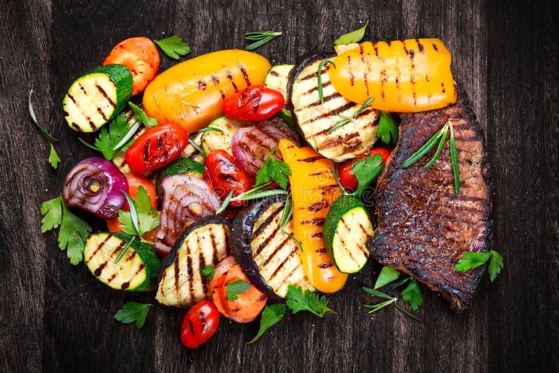 Rundvleeslapje vlees en Geroosterde groenten Op achtergrond van de knipsel de donkere raad stock foto