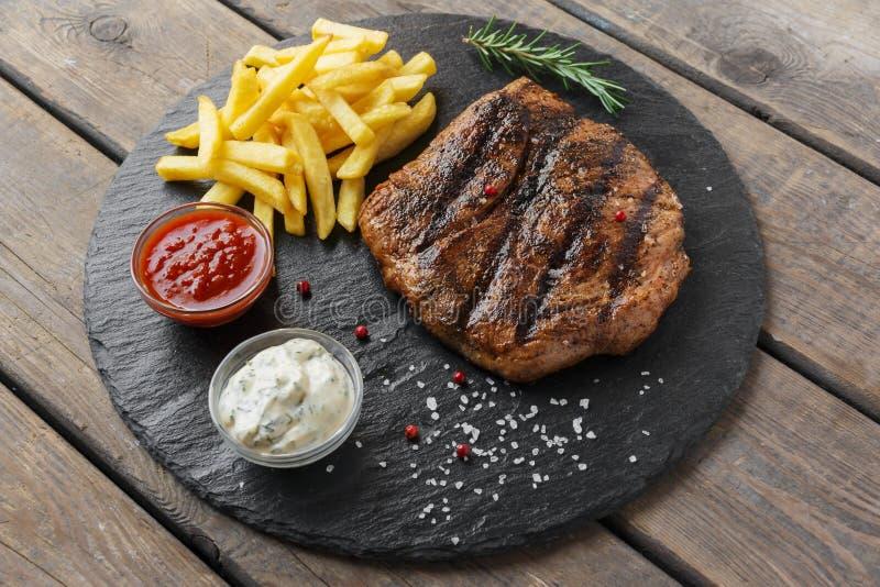 Rundvleeslapje vlees met frieten en saus stock afbeeldingen