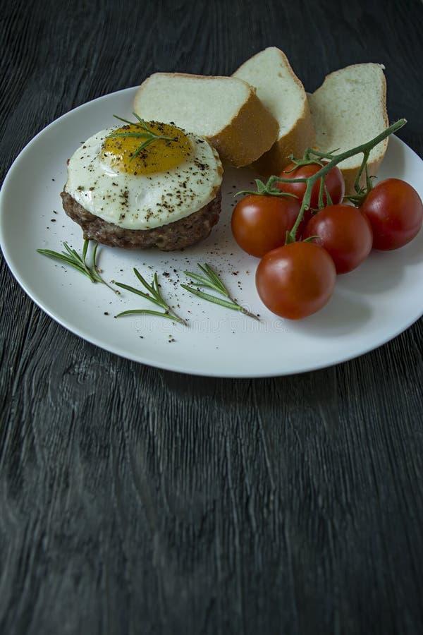 Rundvleeslapje vlees met gebraden ei in kruiden Verfraaid met rozemarijn, verse kers en boterhammen Filed op een witte plaat donk royalty-vrije stock foto