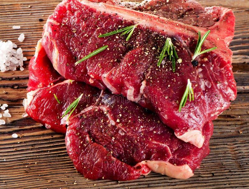 Rundvleeslapje vlees met Kruiden en verse kruiden op houten raad stock afbeeldingen