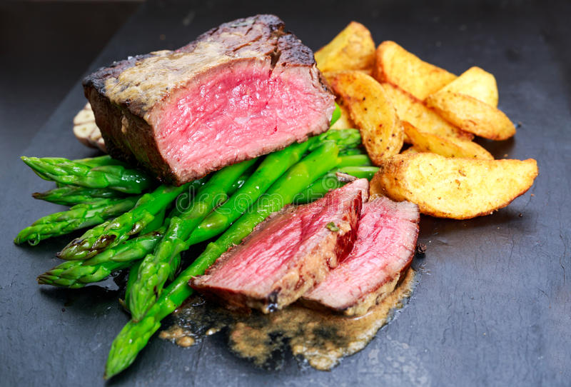 Rundvleeslapje vlees Mignon met Asperge, aardappels, knoflook en tomaten wordt gekookt die stock foto's