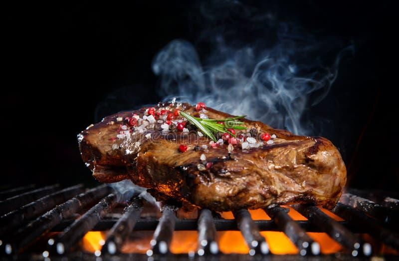 Rundvleeslapje vlees op de grillrooster, vlammen op achtergrond stock afbeelding