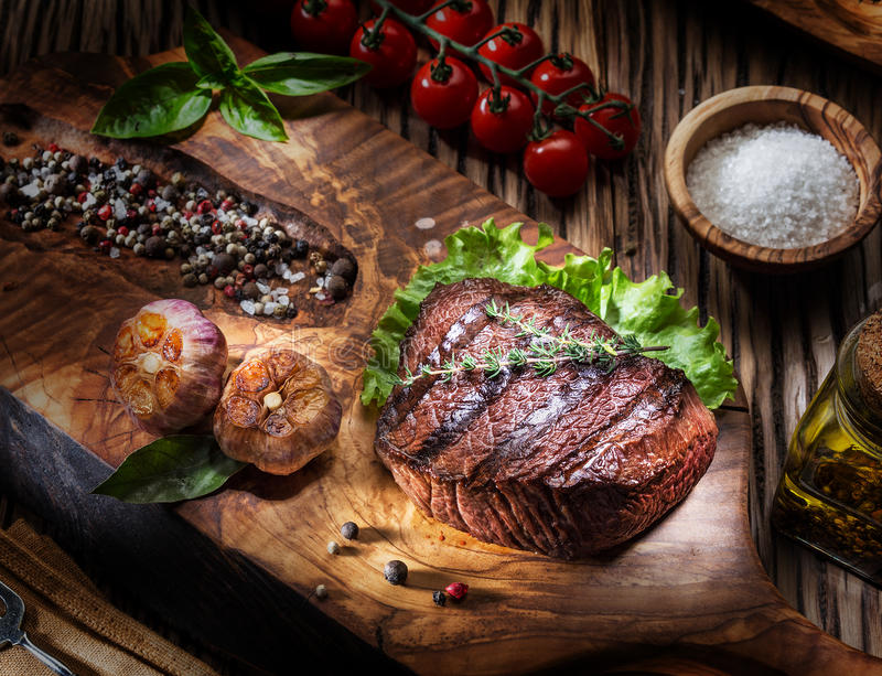 Rundvleeslapjes vlees met kruiden op een houten dienblad stock foto