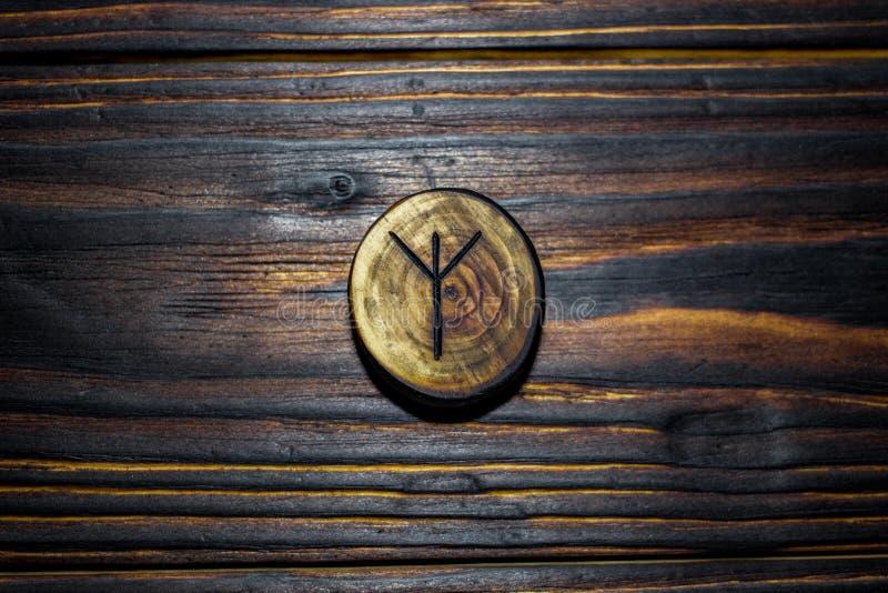 Rune Algiz Elhaz dat van hout op een houten achtergrond wordt gesneden stock foto