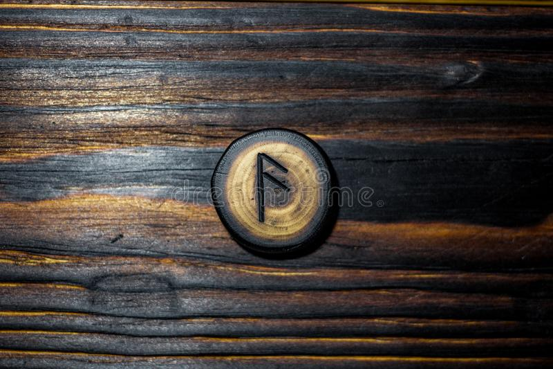 Rune Ansuz van hout op een houten achtergrond wordt gesneden die stock foto