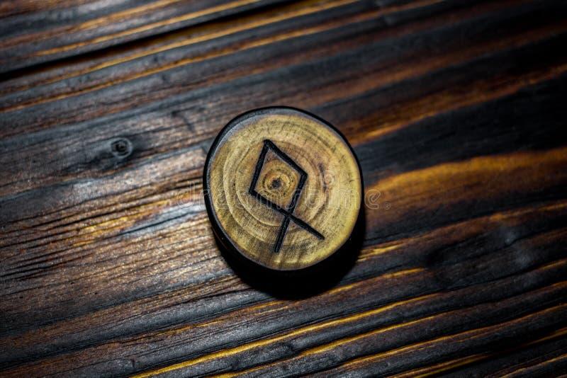 Rune Dagaz schnitzte vom Holz auf einem hölzernen backgroundRune Odal Othala schnitzte vom Holz auf einem hölzernen Hintergrund lizenzfreie stockfotografie