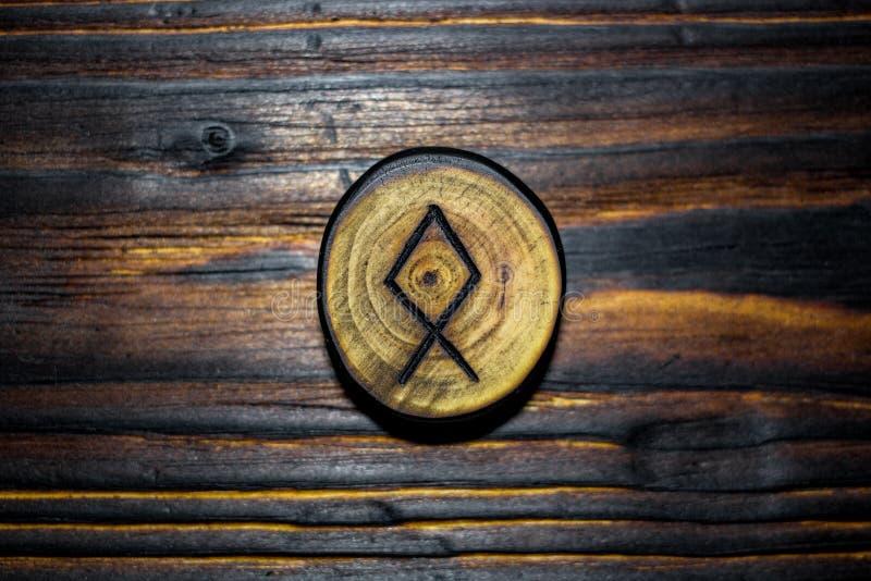 Rune Dagaz schnitzte vom Holz auf einem hölzernen backgroundRune Odal Othala schnitzte vom Holz auf einem hölzernen Hintergrund stockbild