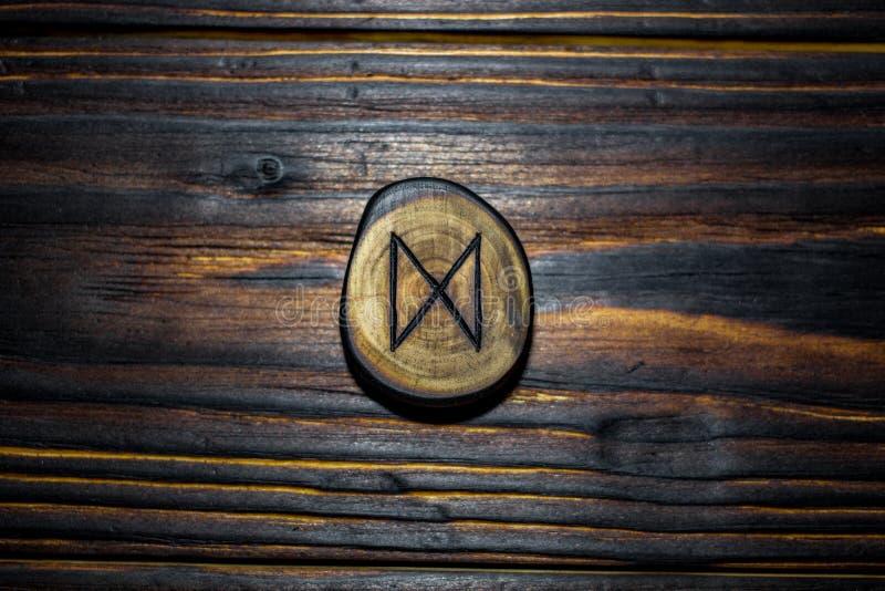 Rune Dagaz van hout op een houten achtergrond wordt gesneden die stock foto