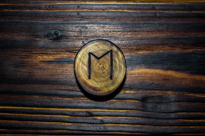 Rune Ehwaz dat van hout op een houten achtergrond wordt gesneden stock foto