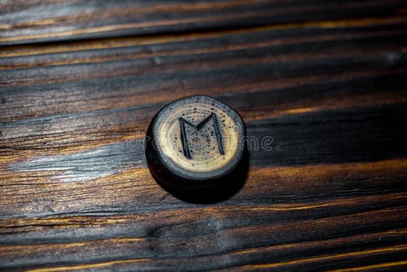 Rune Ehwaz schnitzte vom Holz auf einem hölzernen Hintergrund lizenzfreie stockfotos